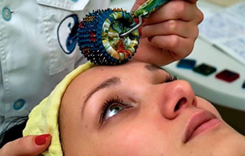 Врач выполняет массаж лица у пациента при помощи Лицевого валика Ляпко